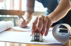 Architekci piszą do domu na modela domu czerwieni, lewa ręka chwyty Fotografia Stock