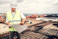 Architekt auf Baustelle mit Plänen und Hardhat Weinlesefilter redigieren lizenzfreies stockfoto