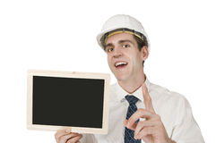 Architekt with black board mouth open. Frontal waist up a young man in a white shirt and White Helmet a small chalkboard continued high with the index finger Stock Images