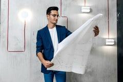Architekt in den Gläsern gekleidet in den blauen karierten Jacken- und Jeansarbeiten mit Plänen auf dem Hintergrund des Betons stockfotos