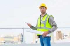 Architekt, der draußen Pläne und Klemmbrett hält Stockfotografie