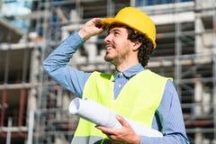 Architekt, der Grundriss an der Baustelle studiert Lizenzfreie Stockfotografie