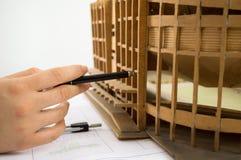Architekt, der seiner Planung nahe bei einer Miniatur hinzufügt Lizenzfreie Stockfotos