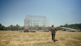 Architekt im Sturzhelm, der in Richtung zum Metallbau auf Hintergrund, zur Ansicht der Natur mit Strohfeld und zum blauen Himmel  stock footage