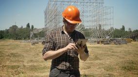 Architekt im Sturzhelm und in den Gläsern unter Verwendung der Tablette und Stellung auf Strohfeld, Metallbau auf dem Hintergrund stock video footage