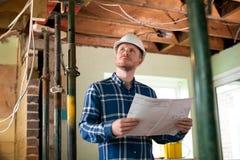 Architekt Inside House Being erneuerte das Studieren von Plänen stockfoto