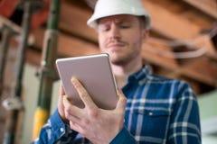Architekt Inside House Being erneuerte unter Verwendung Digital-Tablets stockbild