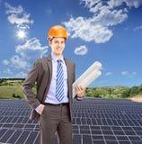 Architekt jest ubranym hełm i trzyma projekty, z słonecznym fotem Obrazy Stock