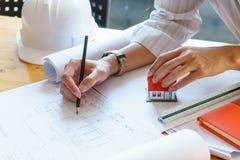 Architekt lub inżynier pracuje na projekcie przy miejsce pracy na drewnianym biurku - architektoniczny projekt, budowy pojęcie fotografia stock