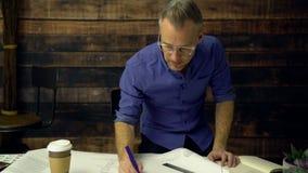 Architekt pije kaw pracy przy brulionowość stołem zbiory