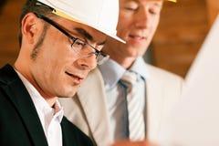 Architekt und Aufbauingenieur, der Pläne behandelt Stockbild