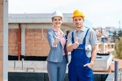 Architekt und Bauarbeiter auf dem Standort, der Daumen-oben gibt stockfotografie