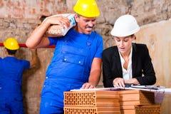 Architekt und Bauarbeiter auf Standort mit Plan Stockfotos