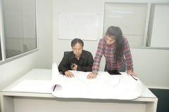 Architekt und Bauingenieur, die Plan im Büro besprechen Lizenzfreie Stockbilder