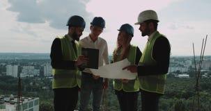 Architekt und Vorarbeiter mit einem Erbauer, der Bauvorhaben auf den Blättern überprüft stock video