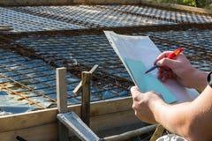 Architekt utrzymuje papiery z spojrzeniami przy i projektem Zdjęcie Stock
