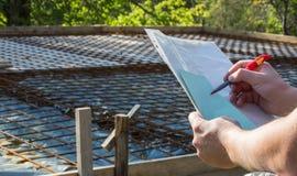 Architekt utrzymuje papiery z spojrzeniami przy i projektem Obraz Stock
