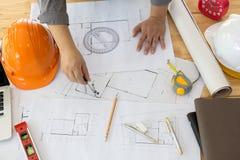 Architekt Working On Blueprint Architektenarbeitsplatz - Architekturprojekt, Pläne, Machthaber, Taschenrechner, Laptop und Teiler Lizenzfreies Stockfoto