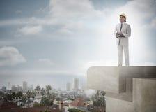 Architekt z ciężkim kapeluszem i schowkiem przeciw pejzażowi miejskiemu i niebu Obraz Stock