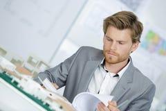 Architekt z modelami i biurowym biurkiem obraz stock