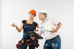 Architekta mężczyzna jest ubranym ciężkiego kapeluszu lub budowniczego kobiety przegląda projekty hełma i współpracownika obrazy stock