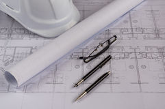 Architekta miejsce pracy - architektoniczni projekty z pomiarową taśmą, zbawczy hełm szkła i napędzać ołówek na stole, wierzchołe Zdjęcia Royalty Free