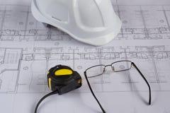 Architekta miejsce pracy - architektoniczni projekty z pomiarową taśmą, zbawczym hełmem i szkłami na stole, Odgórny widok Zdjęcia Royalty Free