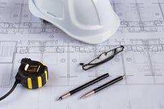 Architekta miejsce pracy - architektoniczni projekty z pomiarową taśmą, zbawczym hełmem i szkłami na stole, Odgórny widok Obraz Royalty Free