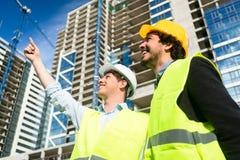 Architekten auf der Großbaustelle, die Anweisungen erteilt stockfotos