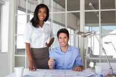 Architekten, die an Bauplänen arbeiten Lizenzfreie Stockfotos