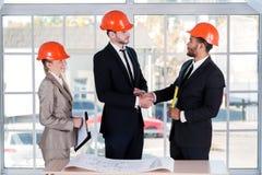 Architekten, die Hände rütteln Drei Architekten getroffen im Büro Lizenzfreie Stockfotos