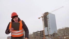 Architekten-Mannarbeitskraft des Erbauers rüttelt schlechte Hände im Sturzhelm und in der orange Weste vor dem hintergrund eines  stock video