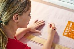 4 Architekten-Studenten-Doing College Homework-Zeichnungs-Linien auf Plan Lizenzfreie Stockfotos