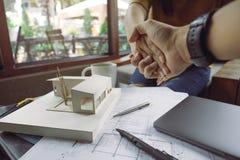 Architekten und Geschäftsmann, die Hand mit Architekturmodell mit Shopzeichenpapier rütteln stockfoto