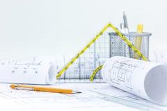 Architektenarbeitsplatz mit Rollen von Plänen und von technischen Plänen stockbilder