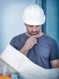Architektenerbauer, der Planplan der Räume studiert Stockfoto