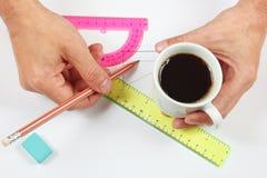 Architektenhände mit einem Tasse Kaffee und einem Bleistift über Arbeitsplatz Lizenzfreie Stockfotos