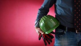 Architekteningenieurarbeitskraft mit Sturzhelm und Handschuhen in der Hand Gebäude lizenzfreies stockbild