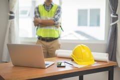 Architektenmann, der mit Laptop und Plänen, Ingenieurinspektion an dem Arbeitsplatz für Architekturplan, einen Bau skizzierend ar stockbilder