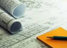 Architektenrollen und -pläne mit orange klebrigen Anmerkungen und Bleistift A lizenzfreie stockbilder
