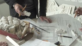 Architektenstärkungsmittel, die bei Tisch mit Skizzen und Gipsdetails im modernen Büro arbeiten stock footage