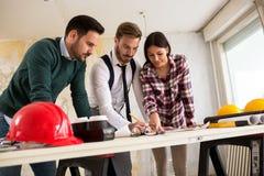 Architektenteam, das über Pläne sich bespricht Lizenzfreies Stockbild