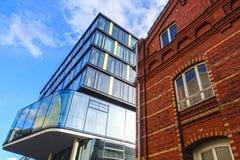 Architektur, modernes Bürogebäude und altes Backsteinhaus Stockbild