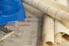 Architekturpläne des Baus - Architekturzeichnungen mit Schutzhelm, Schutzgläsern und Taschenrechner stockfotografie