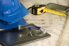 Architekturpläne nahe bei blauem Schutzhelm, Schutzbrillen, Handy, Meter und Tablette stockfotografie