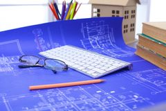 Architekturpläne und Planrollen und Instrumente einer Zeichnung auf dem Worktable lizenzfreies stockfoto