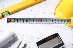 Architekturprojektkonzept Bau plant mit Sturzhelm und Ziehwerkzeugen auf Plänen Lizenzfreies Stockbild