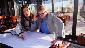 Architekturstudenten, die durch Smartphone zum Lehrer nennen, um nach Zeichnungsprojekt zu fragen stock video footage