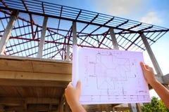 Architekturzeichnungen in der Hand auf Wohnungsbau Lizenzfreies Stockbild