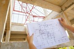 Architekturzeichnungen in der Hand auf Wohnungsbauhintergrund Stockfotos